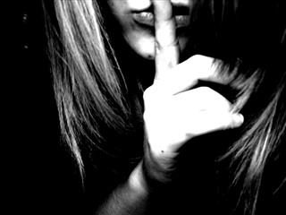 woman holding finger in front of her mouth - shhhhhhh