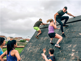 A team of people helping each other climb over a wall - workplace challenges concept
