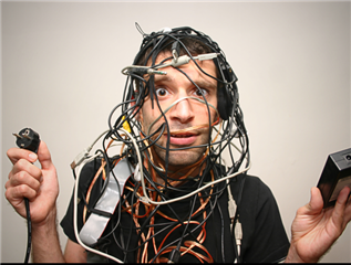 An office worker tangled up in a bunch of computer wires and power cords. - Digital Chaos Concept