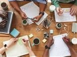 Top view close up of multi-ethnic group of people working together at cluttered wooden table with coffee cups, mugs and stationary items.