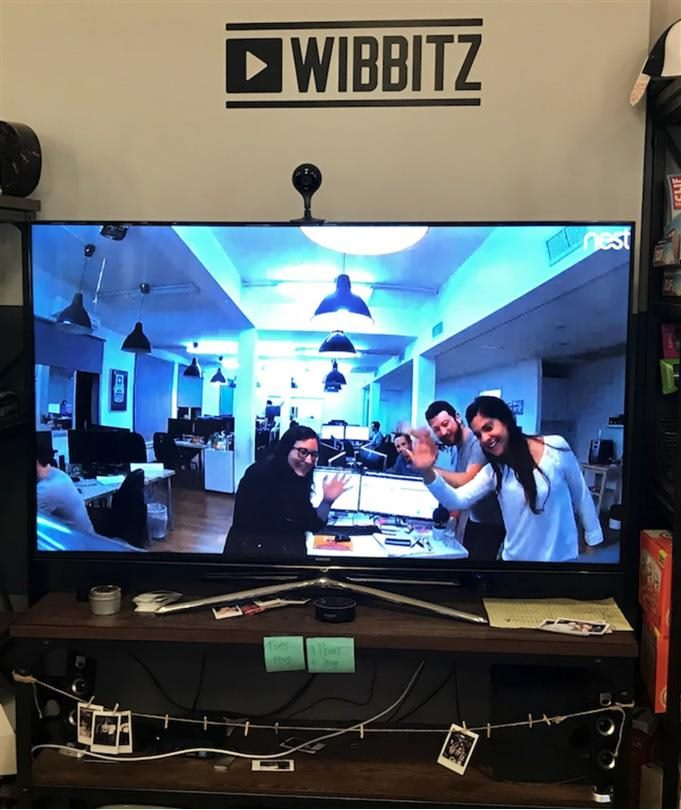 Workers for Wibbitz on a live-streamed video screen wave at the camera.