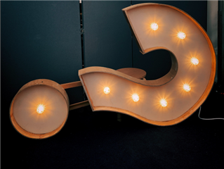 A question mark sign on its side, with lighted bulbs on a dark background - big question concept