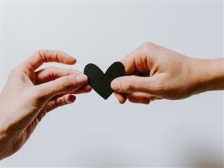 man and a woman holding a paper cutout of a heart