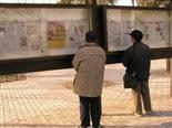 Two men look at kiosks where a daily newspaper is posted.