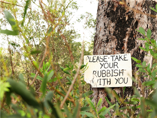 An old warning sign hung on a tree in the woods. The sign says Please take your rubbish with you