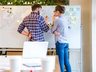 Two people building a strategy on the whiteboard.