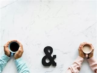 close up of two people's hands holding coffee cups with an ampersand between them