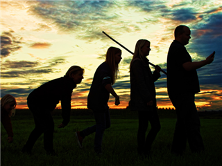 five silhouetted people walking in a  line with a green field and a dusk sky as a background, evolution concept