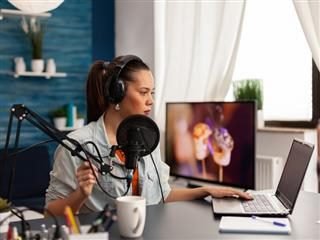 Woman wearing headphones and surrounded by digital equipment including a laptop and microphone.