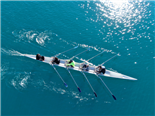 A sport canoe slicing through an emerald green sea. The boat is operated a team of 4 rowers - SEO concept