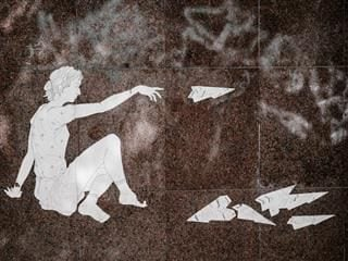 wheatpaste art of a woman throwing paper airplanes