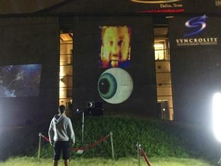 A man looks at a projector screen that has a giant eyeball and a man's face.