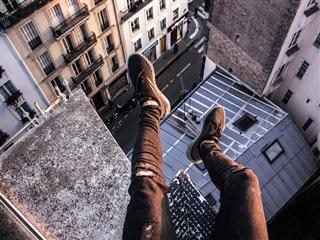 person sitting on top of a building with legs dangling over a high drop