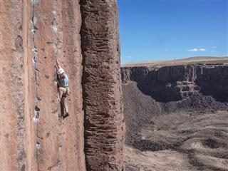 person climbing a sheer rock wall