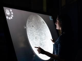 a woman looking at a rendering of the moon in detail on a screen