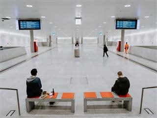 two people sitting and working separately in an empty airport