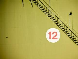number 12 on chartreuse wall with metal staircase overhead