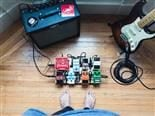 bare feet near a group of guitar pedals with cords plugged in