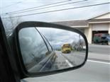 Rear-view mirror with a school bus in the rear.