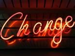 A neon sign that says Change - digitally transforming the digital workplace using change management concept