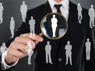A hiring manager looking at silhouetted job candidates through a magnifying glass