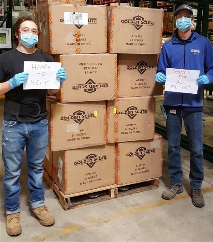 Magid workers hold up signs as they flank boxes they are about to donate to Chicago-area first-responders.