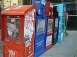 Row of newspaper boxes on a street.