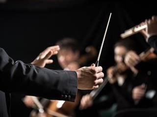 conductor with baton in front of an orchestra