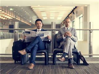 Two men sitting on a bench reading newspapers in a airport terminal read