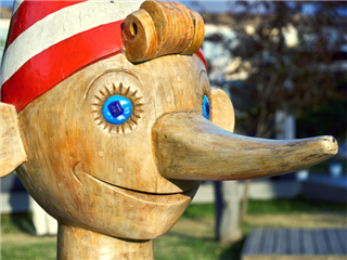 ead of wooden Pinocchio sculpture standing outdoors - lying to investors concept.