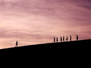 follow the leader: group of people walking down a hill with one person visibly in the lead