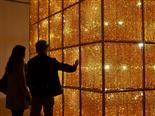 A woman and a man are looking at a large cube of crystals backlit by lightbulbs.