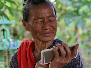 Older Thai woman uses iphone