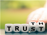 "Hand turns dice and changes the word ""Trust"" to ""Truth""."