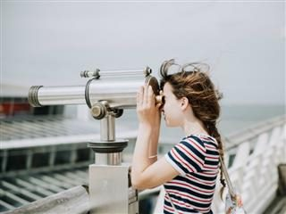 young woman looking through a telescope