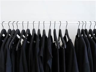 a rack of black clothing against a white background