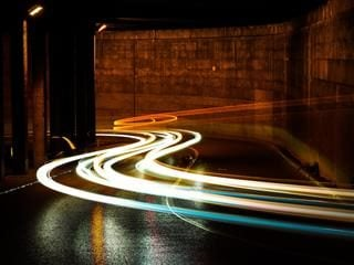time lapse photograph of car headlights driving through a tunnel