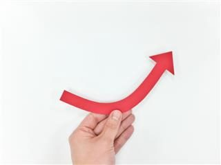 hand holding an upward facing arrow in the shape of a smile