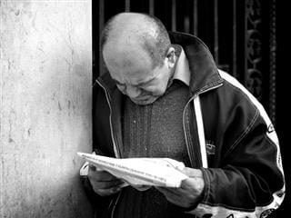 man leaning up against a wall reading a newspaper.