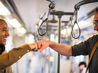 two guys fist bumping on the subway