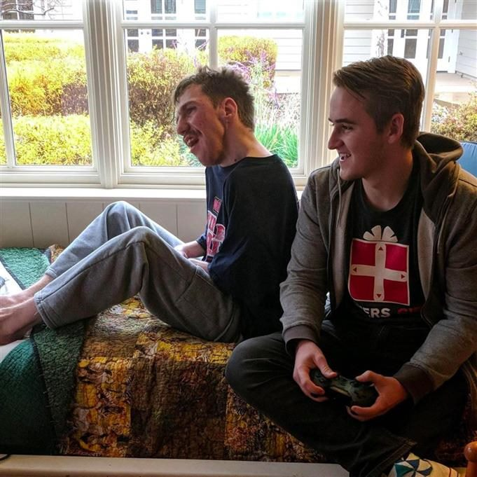 Dillon Hill plays video games with a man who has a handicap.