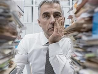 man surrounded by stacks of folders