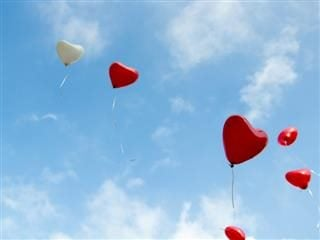 heart shaped balloons floating up into a clear blue  sky