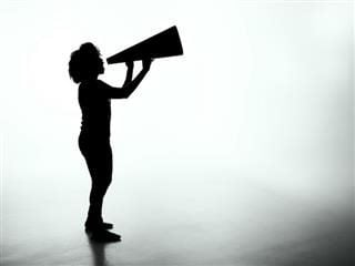 silhouette of  a woman holding a megaphone against a blank background
