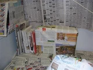 books bundled up in newspapers, and a wall with newspapers taped to it.