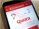 The quora website displayed on a smartphone, sitting on a desk - Quora Marketing concept