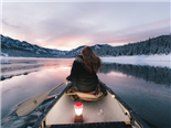 woman canoeing in river between snow covered mountains