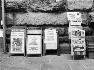 Several newspapers displayed on a city street sidewalk - newsbyte concept