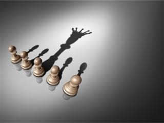 Chess pawns in a row with shadows. One chess pawn's shadow looks like the king.