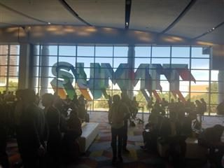"Attendees of Adobe Summit in front of a large, glass window with the word ""Summit"" on it."